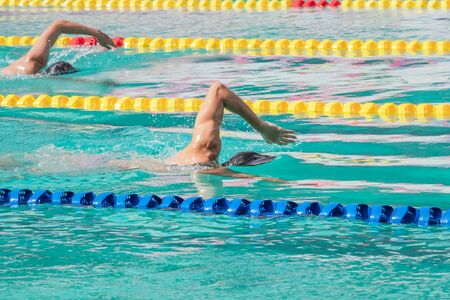 Movement of athletic swimmers swimming freestyle stroke front crawl or forward crawl during competition in to the pool