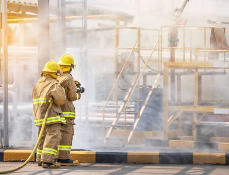 professional firemen brave buddy team assistance in yellow fire fighter uniform holding fire hose nozzle fighting with fire flame in the industrial factory