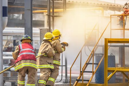 Action professional firemans in yellow fire fighter uniform holding fire hose nozzle spraying foam water control fighting in the industrial factory