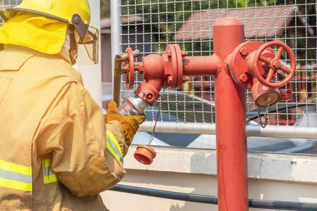 Fireman in yellow fire fighter uniform during connect firehose tube in to fire hydrant during basic fire fighting training