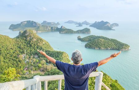 the man standing raising hands open arms achievements successful and celebrate enjoy on high cliff Pha Jun Jaras view point after climbing to the peak of mountain at Wua Ta Lap island Surat Thani, Thailand summer holidays concept