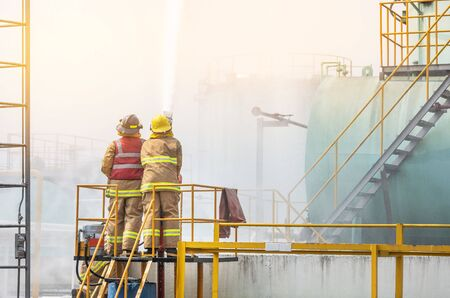 Action professional firemen brave buddy team assistance in yellow fire fighter uniform holding fire hose nozzle spraying foam  water control fighting in the industrial factory