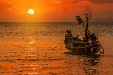 Silhouette longtail boat fishing boat moored on tropical beach  at fisherman village during sunset twilight time Samui, Thailand
