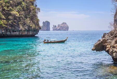 Landscape viewpoint of loh samah bay with longtail boat and turquoise lagoon is famous tour snorkeling point at phi phi island, krabi Thailand