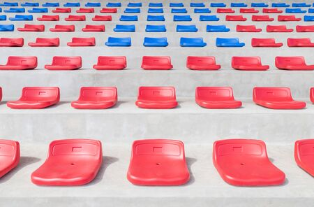 Rows of empty red and blue sport plastic seats grandstand in public sport stadium