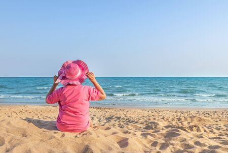 Back view woman with pink straw sun hat sitting alone relax enjoying on the beach look in the sea. copyspace on the right