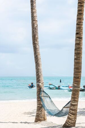 Empty old hammock for relaxation under coconut palm trees on sandy tropical beach at Wua Ta Lap island beach in Angthong Islands National Marine Park Surat Thani, Thailand, Travel summer holiday concept.