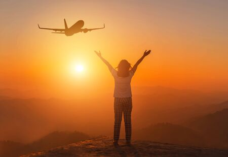 Silhouette back of woman stand raising up two arm celebrate enjoying on high cliff mountain with airplane flying in sunset time,      freedom destination travel concept