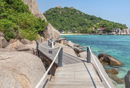 Landscape view of old wooden walkway bridge through the rock at Koh Nang Yuan Island under blue sky in summer day Koh Nang Yuan Island is most popular famous tourist attractions in the gulf of Thailand, Surat Thani, Thailand