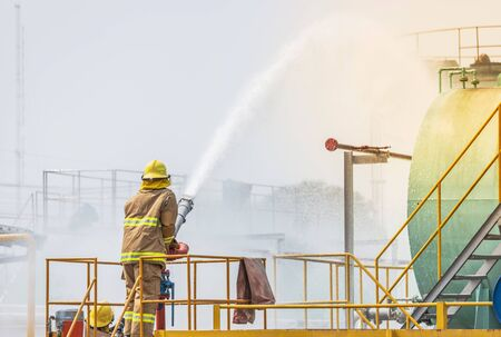 Action professional fireman in yellow fire fighter uniform holding fire hose nozzle spraying foam  water control fighting in the industrial factory