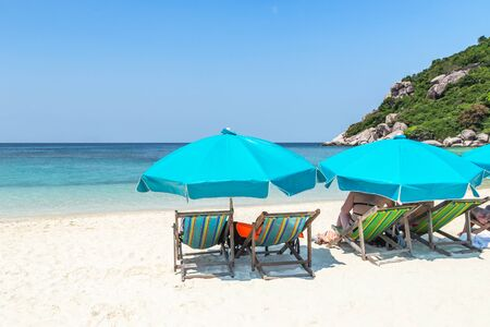 Landscape view of row blue umbrellas with wooden beach chairs on tropical sandy beach in sunny day at Koh Nang Yuan Island Surat Thani, Thailand summer holidays concept relax leisure concept Archivio Fotografico - 134772644