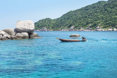Landscape view with long tail boat sailing in turquoise sea between Koh Nang Yuan Island and Koh Tao Island under blue sky in summer day Koh Nang Yuan Island is most popular famous tourist attractions in the gulf of Thailand, Surat Thani, Thailand 免版税图像