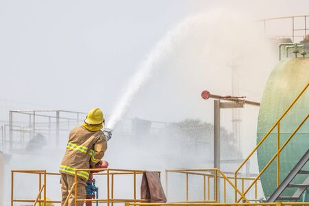 Action professional fireman in yellow fire fighter uniform holding fire hose nozzle spraying foam water control fighting in the industrial factory 免版税图像
