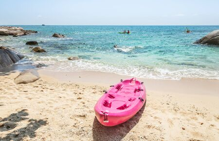 Pink kayaks moored on the beach with turquoise sea in sunny day destination summer holiday concept