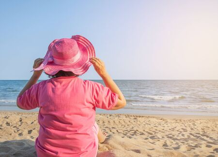 Back view woman with pink straw sun hat sitting alone relax enjoying on the beach look in the sea. Stockfoto