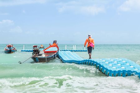 The man walking on plastic pontoon walk way floating in the sea during the sea is very rough wave height of the strong wind