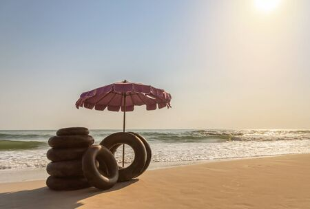 Landscape view beach umbrella with ring lifebuoys on tropical sandy beach in the morning summer holidays concept Stockfoto