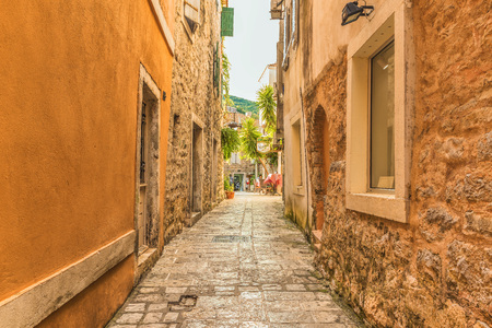 Budva, Montenegro - August 22, 2017: Old Town Street Budva, Montenegro. The first mention of this city is more than 26 centuries ago. We see ancient houses, a very narrow street, cafes, shops.