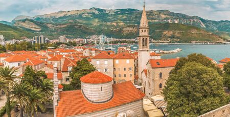 Panorama of the Old Town of Budva: ancient walls, buildings with a red tile roof - its something like a mini Dubrovnik in Croatia. Budva is one of the best preserved medieval Mediterranean towns and the most popular resorts of the Adriatic Riviera.