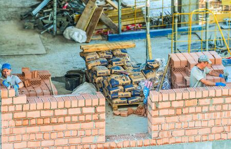 Kiev, Ukraine - June 22, 2018: The workers are working on the construction site. Works on laying a wall of a red brick are being carried out. 新聞圖片