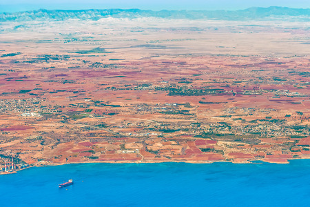 View of the island of Cyprus in the region of the bay of Dhekelia. Fragment of a power station, a sea dock, a villa and a village, a road and a mountain massif. Stock Photo