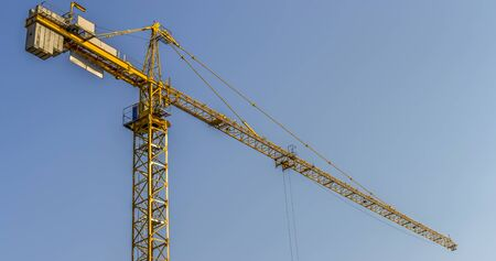 Tower crane at a construction site on a background of blue sky - panorama. Stock fotó - 129488364