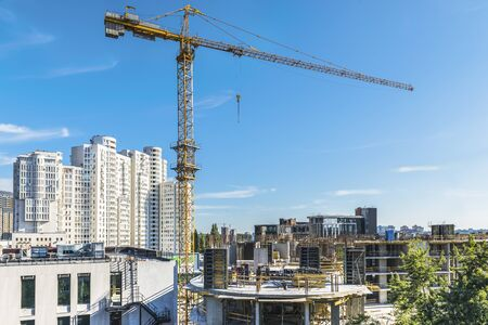 A fragment of the city of Kiev, Ukraine. In the foreground are tower cranes over one of the new buildings, as well as constructed residential and office buildings. Stock fotó - 129488513