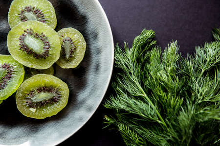 dried kiwi, dill and plate in raku-yaki style on a black background
