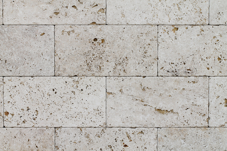 Natural Italian stone. Smooth travertine surface. A sample of wall cladding with natural stone.
