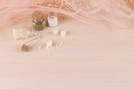 Delicate background with peach fabric, beads and needles. Creation