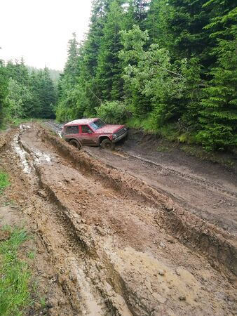 The red car stuck off-road. Extreme travel.