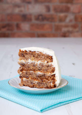 A piece of hummingbird cake on the white table, brick wall background Stock Photo
