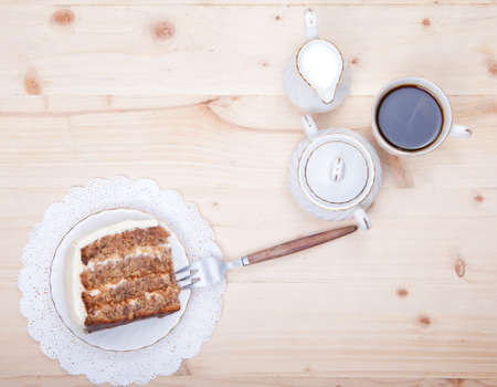 rich flavor: Piece of carrot cake coffee and milk on the white wooden table, top view Stock Photo