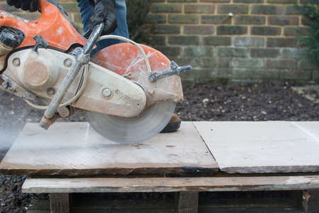 stone cutter: Man using the discutter in the garden to cut the indian sandstone slabs; picture in motion Stock Photo