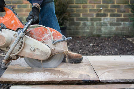 Man using the discutter in the garden to cut the indian sandstone slabs; picture in motion Stock Photo