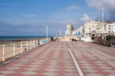 Hastings promenade, East Sussex, England, view to the west of the pier, selective focus on the nearest palm tree on the right Stock Photo