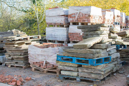 scrapped: Reclamation yard background: stacks of paving slabs and reclaimed bricks on the pallets, selecive focus