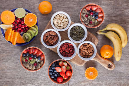 Smoothie  with fruits and berries on the grey wooden table, with variety of fruits and nuts around, selective focus; top view Stock Photo