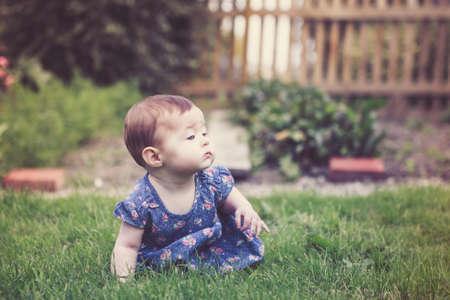 Baby girl crawling on the grass in the garden, selective focus Reklamní fotografie