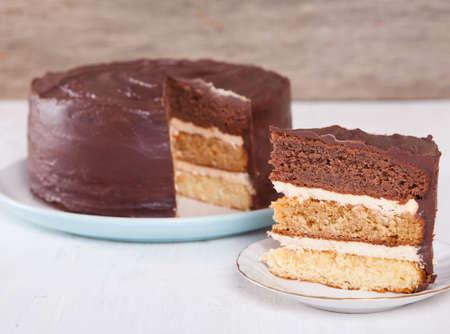 ganache: Chocolate, caramel and vanilla layered cake with chocolate ganache on the white table