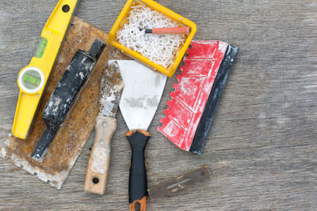 Old used tools for tiling on the rustic wooden background, selective focus Stock Photo