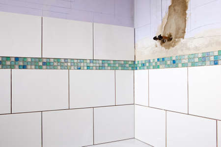 tiling: Home improvement: tiling bathroom walls, fitting the pipes for the shower Stock Photo
