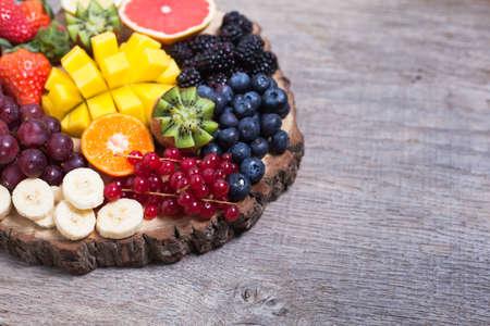 Raw fruit and berries platter, mango, kiwis, strawberries, blueberries, blackberries, red currants, grapes, selective focus Stock Photo