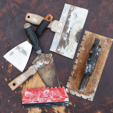 tiling: Old used tools for tiling on the rustic wooden background, selective focus Stock Photo