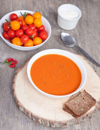 Tomato soup with dried herbs, chilli, tomoatoes and cream on the dark wooden table Stock Photo