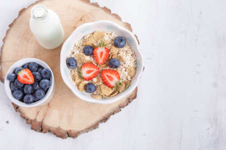 Breakfast: oatmeal cereals with berries on the white wooden table, selective focus
