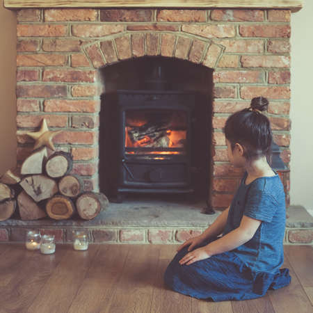 woodburner: Little girl sitting in front of the fireplace looking at the fire flame in the woodburner, dark toned photo, selective focus, square