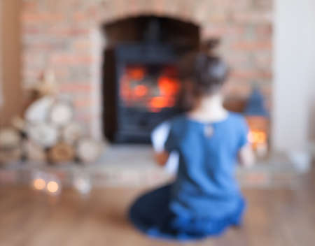 woodburner: Abstract blurred photo of little girl sitting in front of the fireplace looking at the fire flame in the woodburner, selective focus