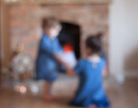 woodburner: Abstract blurred background of two little girls in front of the fireplace
