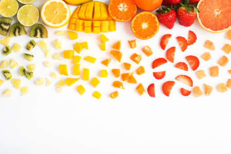 Top view of red, orange, yellow, green fruits with cut pieces on the white background